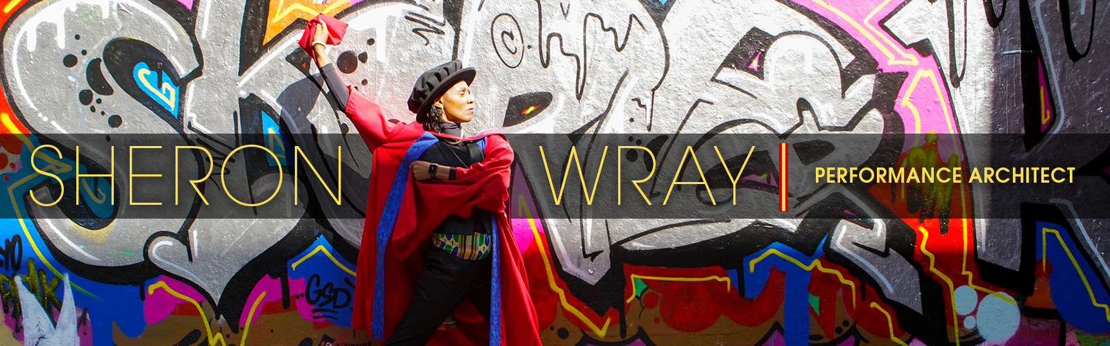 Sheron Wray: Performance Architect header with the artist posed in her doctoral robes in front of a graffiti filled wall.